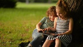 Deux enfants mignons à l'aide du comprimé numérique dans le jardin d'été clips vidéos