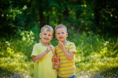 Deux enfants mignons, ami, eau potable en parc dans l Photos libres de droits
