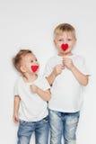 Deux enfants mignons avec de petits coeurs rouges sur leur bouche Photographie stock libre de droits