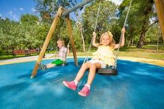 Deux enfants mignons balançant sur le terrain de jeu Images stock