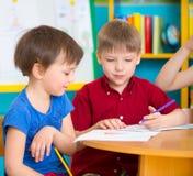 Deux enfants mignons dessinant au jardin d'enfants Images stock