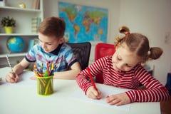 Deux enfants mignons dessinant avec les crayons colorés Images stock