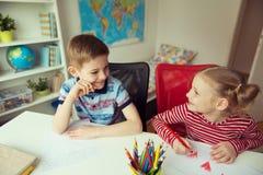 Deux enfants mignons dessinant avec les crayons colorés Photographie stock libre de droits