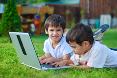 Deux enfants mignons s'étend dans l'herbe sur l'ordinateur portatif Photos libres de droits