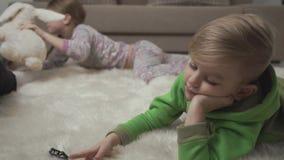 Deux enfants mignons s'étendant sur le tapis pelucheux jouant avec des jouets sur le plancher Week-end heureux d'enfants banque de vidéos