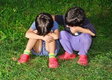 Deux enfants mignons s'asseyant sur la prise de masse Photo libre de droits