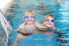 Deux enfants nageant dans la piscine Photographie stock libre de droits
