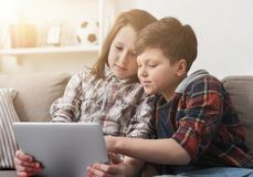 Deux enfants observant le film sur le comprimé numérique à la maison Photo stock