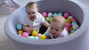Deux enfants ont l'amusement dans une piscine avec les boules en plastique Les garçons comprennent quel amusement est banque de vidéos