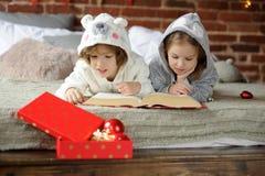 Deux enfants ont lu le livre énorme avec des contes de fées de Noël Photographie stock libre de droits
