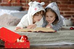 Deux enfants ont lu le livre énorme avec des contes de fées de Noël Image libre de droits