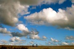 Deux enfants parlant sur la plage avec le grand ciel au-dessus de eux Images libres de droits