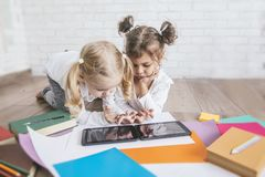 Deux enfants, petites filles de comprimé de observation d'âge préscolaire à h Photos stock