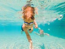 Deux enfants plongeant dans les masques sous l'eau dans la piscine images libres de droits