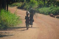 Deux enfants portent les branches et le sac en tant que route poussiéreuse de promenade vers le bas photo libre de droits