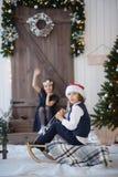 Deux enfants près de la porte en bois décorée des guirlandes et d'une guirlande images stock