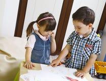 Deux enfants préscolaires apprennent les nombres Photos stock