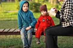 Deux enfants prenant le déjeuner leur dehors dans le parc Photographie stock