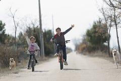 Deux enfants qui vont avec le vélo à l'appareil-photo image stock