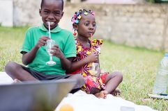 Deux enfants reposant et buvant du jus image stock