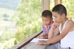 Deux enfants reposent des livres de lecture recherchant la connaissance, Educatio images stock