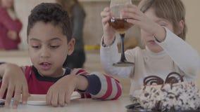Deux enfants s'asseyant à la table à la maison Le garçon blond caucasien de fille et d'afro-américain ont l'amusement ensembl banque de vidéos