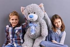 Deux enfants s'asseyant avec le grand ours de nounours Images stock