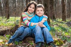 Deux enfants s'asseyant ensemble dans la forêt Images stock
