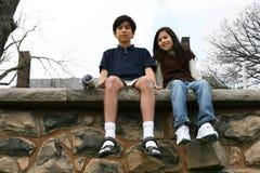 Deux enfants s'asseyant sur la saillie de roche image stock