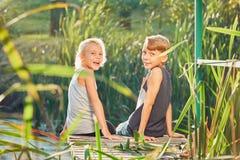 Deux enfants s'asseyant sur le pilier du lac Photo stock