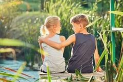 Deux enfants s'asseyant sur le pilier du lac Images stock