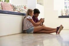 Deux enfants s'asseyant sur le plancher et jouant avec Smartphone Photos stock