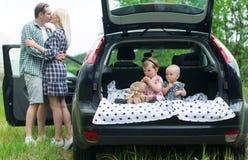 Deux enfants s'asseyent dans un transporteur de bagage de voiture Photo libre de droits