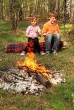 Deux enfants s'asseyent près du feu de camp Image libre de droits
