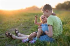 Deux enfants s'asseyent sur l'herbe le soir images stock