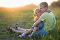 Deux enfants s'asseyent sur l'herbe le soir photographie stock libre de droits