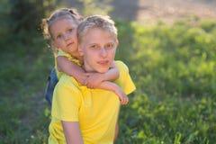 Deux enfants s'asseyent sur l'herbe le soir image stock