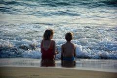 Deux enfants s'asseyent sur la plage directement avant la vague par la mer Images stock