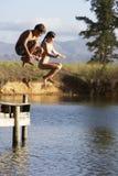 Deux enfants sautant de la jetée dans le lac photo stock