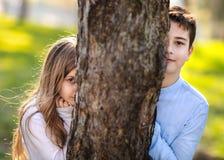 Deux enfants se cachant derrière l'arbre Jeune fille et garçon jouant autour de l'arbre en parc Portraits de deux enfants en parc photos libres de droits