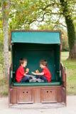 Deux enfants, se reposant dans un banc abrité, jouant les applaudissements GA Image libre de droits