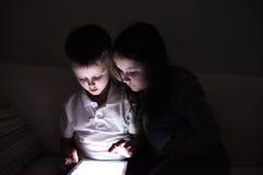 Deux enfants, se reposant dans un foncé, jouant avec le comprimé Photographie stock libre de droits