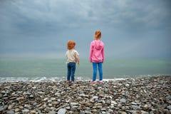Deux enfants se tiennent sur le bord de la mer et le regard dans la distance image stock