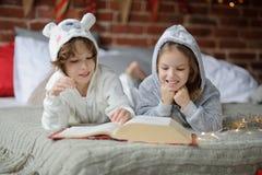 Deux enfants se trouvent sur le grand lit et lisent des contes de fées Image stock