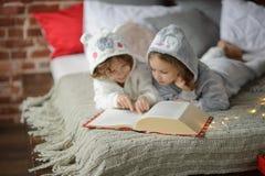 Deux enfants se trouvent sur le grand lit et lisent des contes de fées Images libres de droits