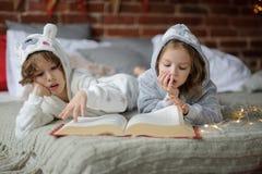 Deux enfants se trouvent sur le grand lit et lisent des contes de fées Photo stock