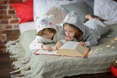 Deux enfants se trouvent sur le grand lit et lisent des contes de fées Photos libres de droits