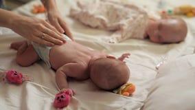 Deux enfants se trouvent sur le lit, on dort, et l'autre maman fait la gymnastique spéciale pour des nouveaux-nés à partir des pr banque de vidéos