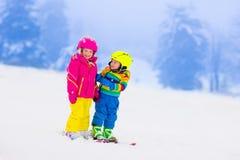 Deux enfants skiant en montagnes neigeuses Photos stock