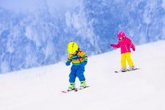 Deux enfants skiant en montagnes neigeuses Image libre de droits